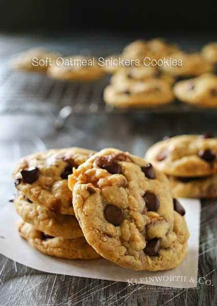 These Soft Oatmeal Snickers Cookies are a thick & chewy oatmeal cookie stuffed full of Snickers candy bars & chocolate chips. So easy & so yummy too! Definitely the best oatmeal cookie recipe around! Don't miss the tip on how to make those chocolate chips look so perfect too!