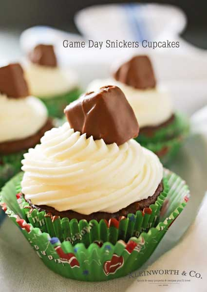 Looking for some game day food ideas? Game Day Snickers Cupcakes are an easy 3 - ingredient cupcake recipe loaded with Snickers candy bars, topped with a delicious & easy buttercream frosting & more Snickers minis. on kleinworthco.com