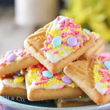 Looking for a quick little treat to serve at all your Easter gatherings? Creating cute treats like these White Chocolate Spring Cookies for Easter is easy. Simple shortbread cookies, white chocolate & Easter sprinkles is so much fun! These literally take about 15 minutes to make & everyone just loves them. People will think you slaved away in the kitchen for hours. They are an adorable Easter dessert that bring BIG smiles!