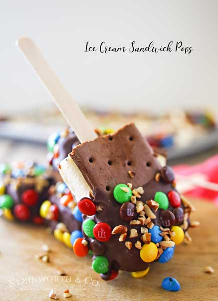 Ice Cream Sandwich Pops are an easy summer treat to make. Made with a simple ice cream sandwich, chocolate & decorations they are a perfect frozen treat. Make some for all of your celebrations, holidays & backyard BBQ's this summer.