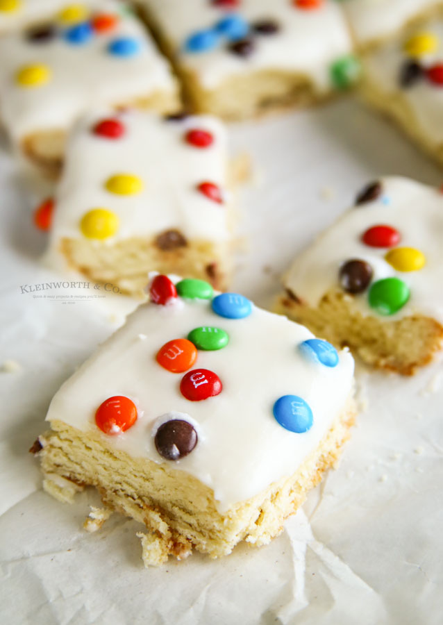 M&M Sugar Cookie Bars - deliciously frosted soft sugar cookie base, topped with mini m&m's. You can't go wrong with these.